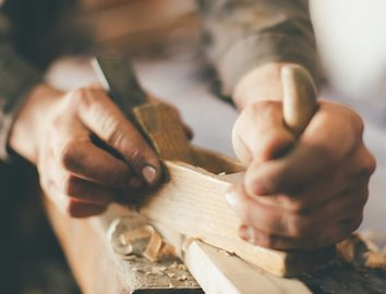 A pair of hands chiseling away at a wooden block