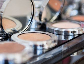 Makeup powders in silver compacts in a line on a shelf