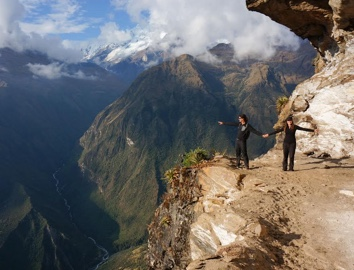 Two people standing on a cliff edge in front of a mountain view