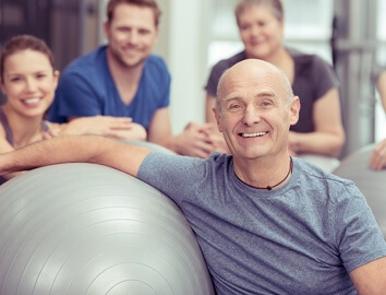 Man leaning against an exercise ball in front of three smiling people